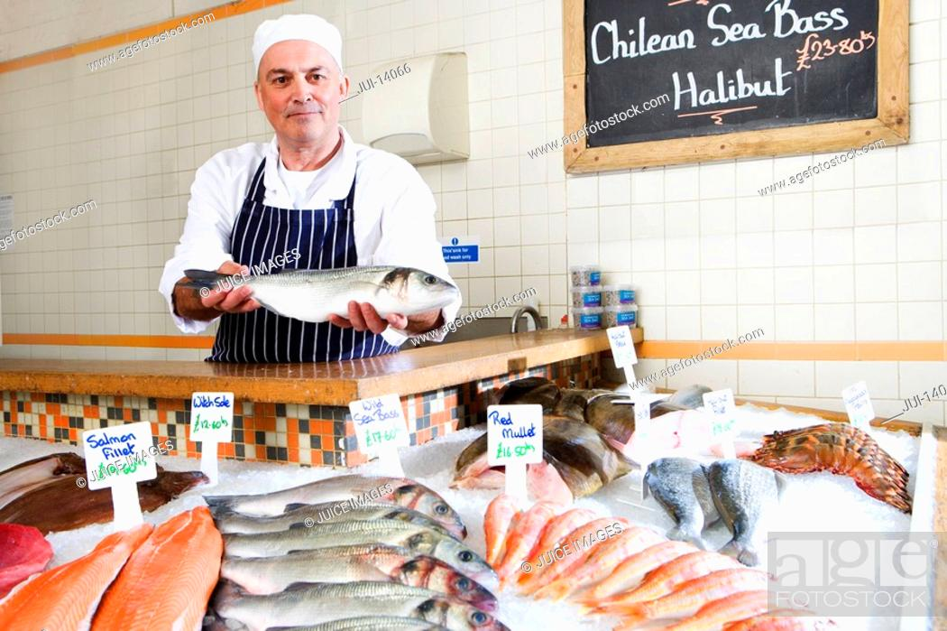 Stock Photo: Fishmonger behind counter in shop, holding out fish, portrait.