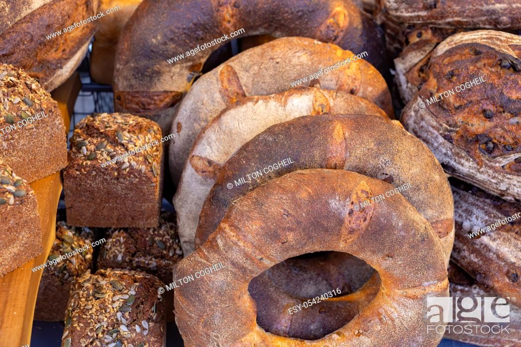 Stock Photo: Variety of freshly baked rustic bread loaves on display on a food market stall in the UK.
