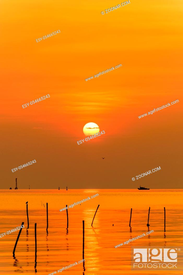 Stock Photo: Beautiful nature landscape bright yellow sun reflecting orange light on the water surface of the sea and golden sunlight in sky.