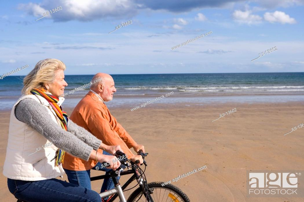 Stock Photo: Senior couple cycling on beach, side view.