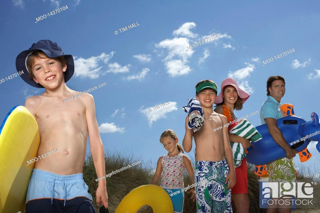 Stock Photo: Parents with three children 6-12 carrying beach accessories.