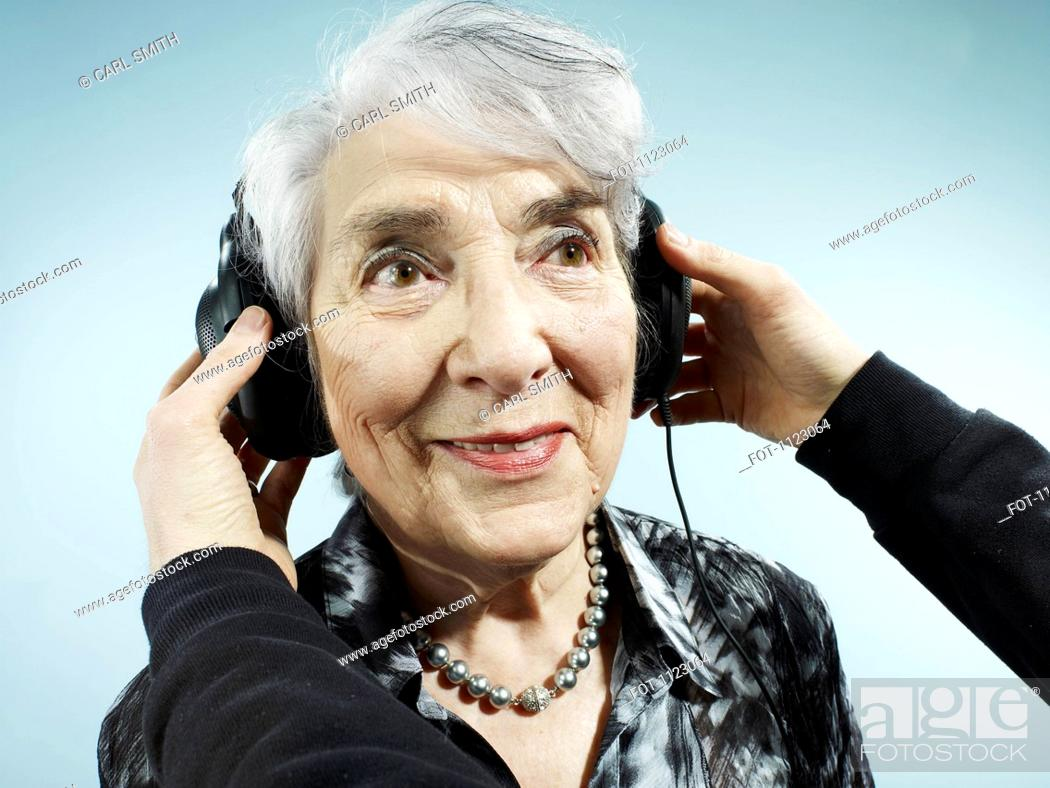 Stock Photo: A person putting headphones on a senior woman.