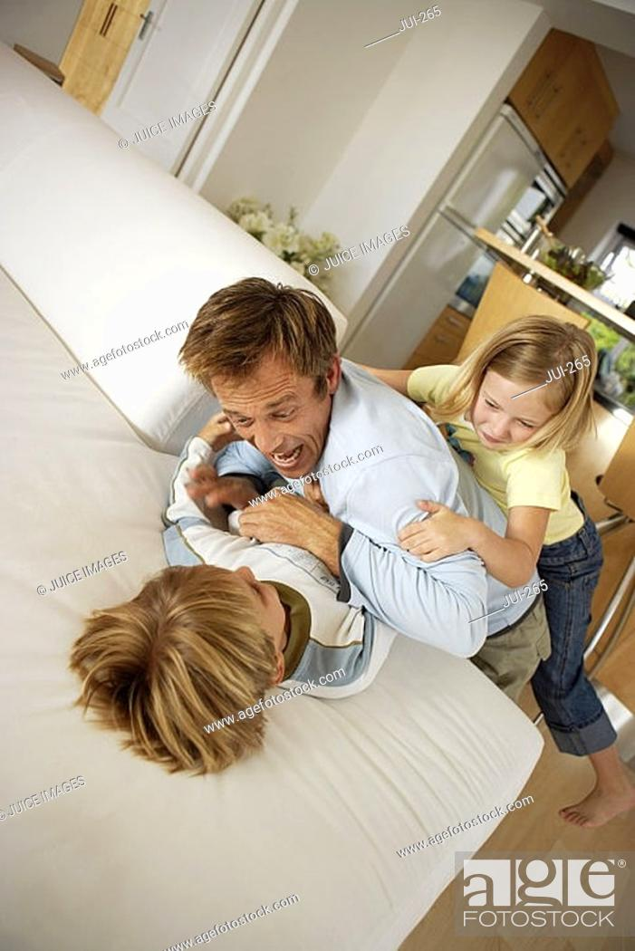 Stock Photo: Father playing with son and daughter 6-8 on sofa at home, elevated view tilt.