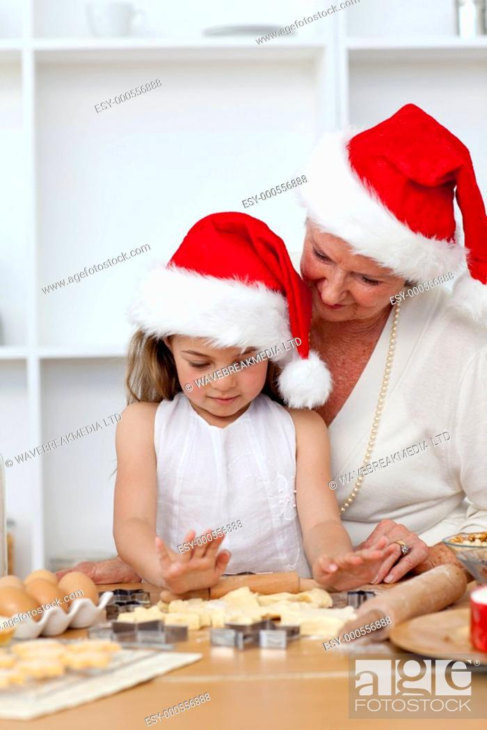 Stock Photo: Grandmother and little girl baking Christmas cakes in the kitchen.