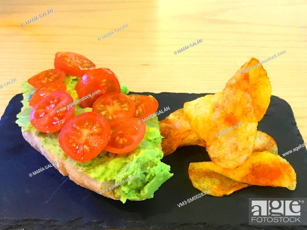 Photo de stock: Guacamole and cherry tomatoes on toast with chips.