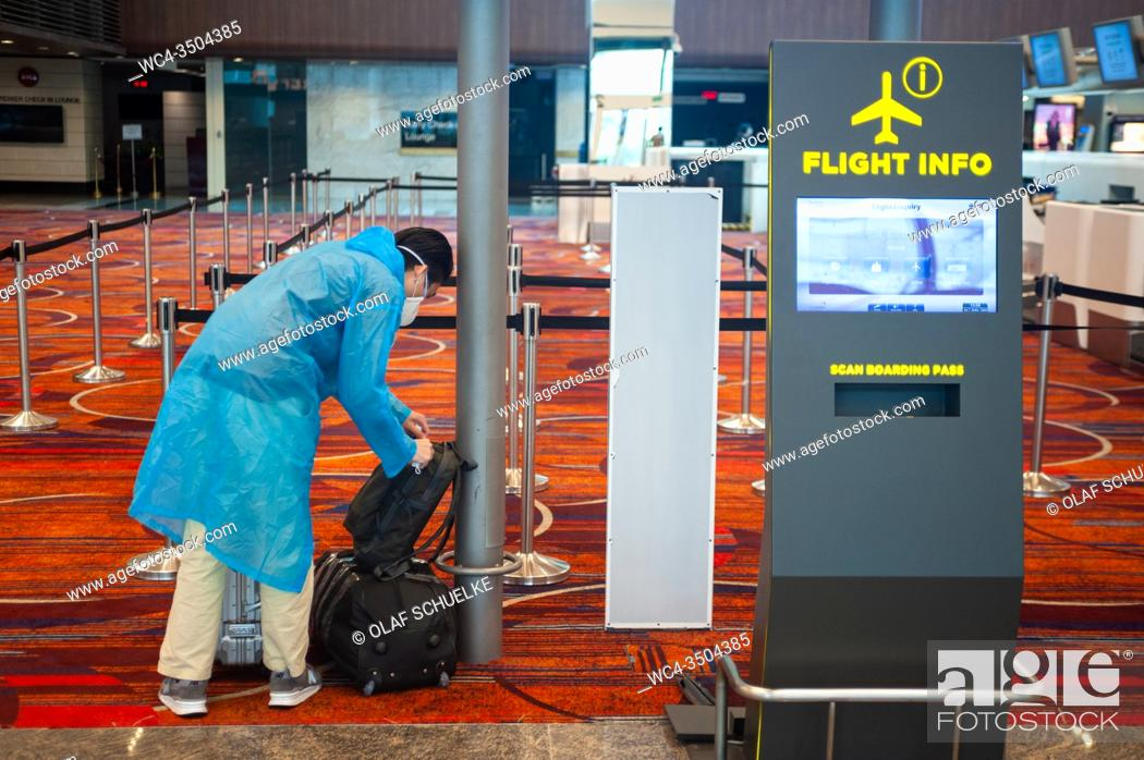 Stock Photo: Singapore, Republic of Singapore, Asia - A passenger at Changi Airport's Terminal 1 wears a protective face mask and a raincoat to prevent an infection with the.