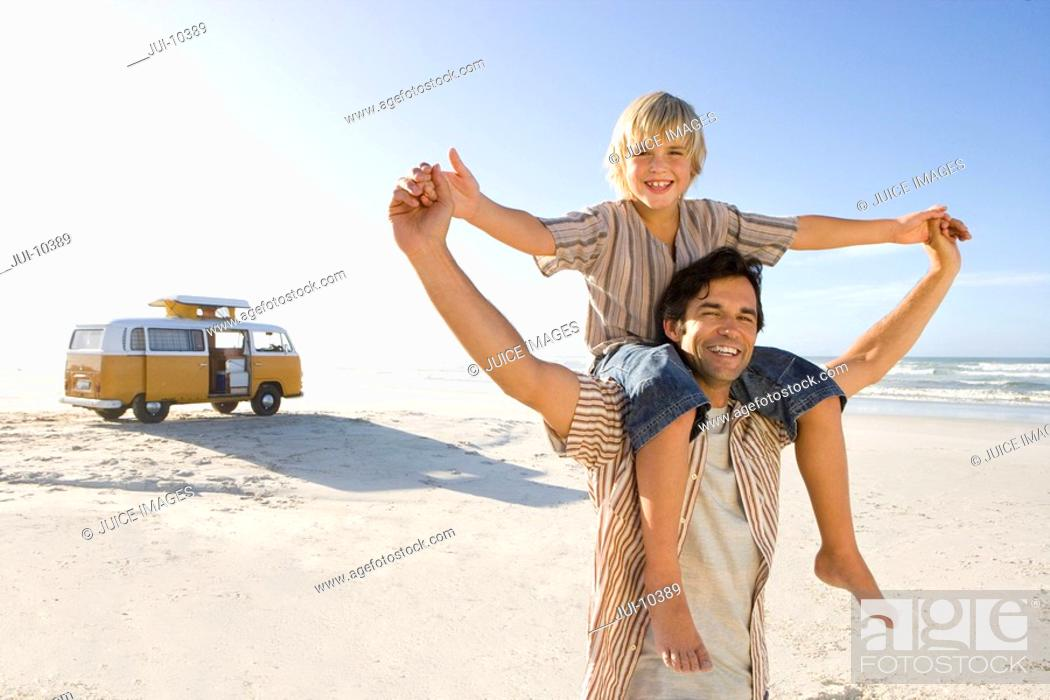 Stock Photo: Boy 6-8 on father's shoulders holding hands on beach, smiling, portrait.