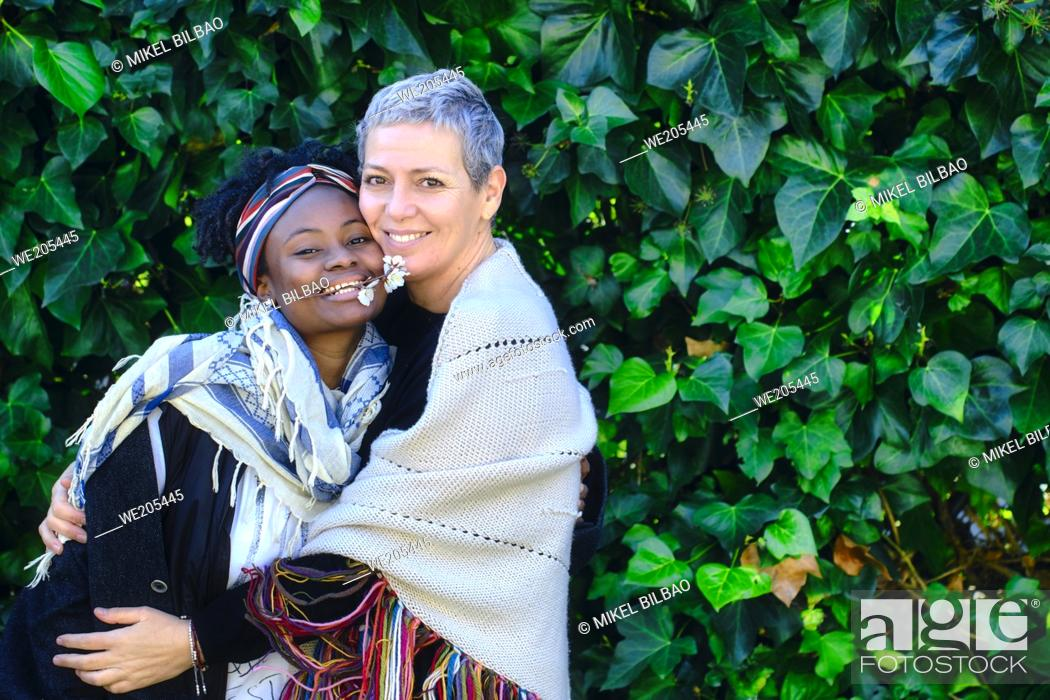 Stock Photo: Mature caucasian woman and african young woman hugging in a garden with a leaves background.