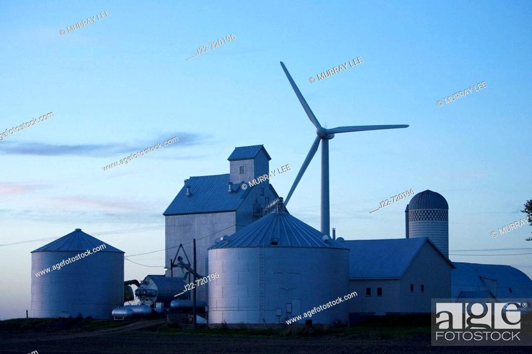 Stock Photo: Modern grain handling facility with wind generator towering over it on Iowa farmstead near Williams, Iowa, USA  Photo shows grain elevator tall structure.