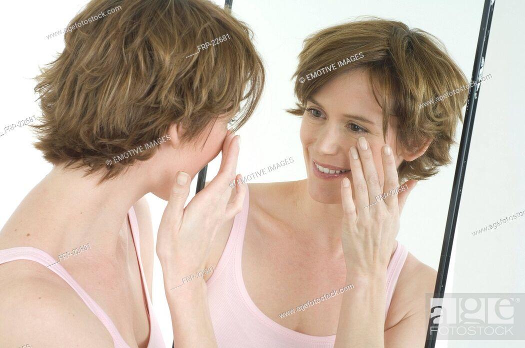 Imagen: Woman looking in mirror.
