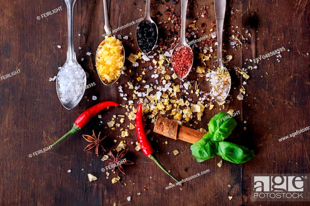 Stock Photo: Variety of salt and spices in spoons on rustic wooden background. Top view.