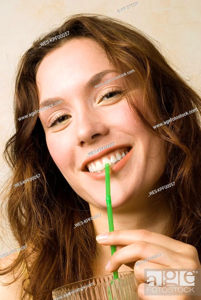 Stock Photo: Young woman, Holding glass and straw, smiling, close up.