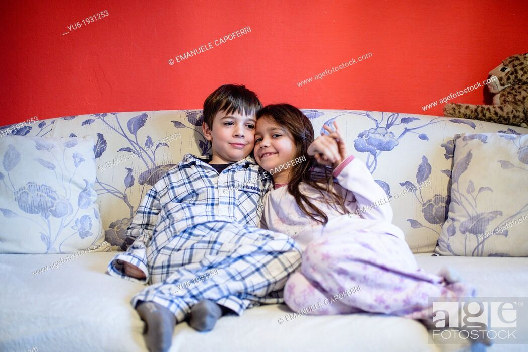 Stock Photo: Children brothers, with his pajamas hugging each on sofa.