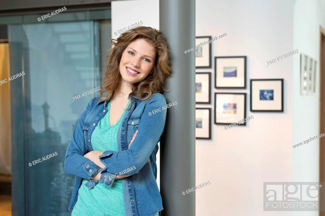 Stock Photo: Happy woman leaning against a column.