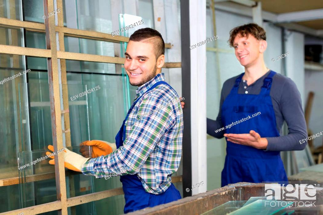 Stock Photo: Two careful american workmen cutting glass for windows at workshop.