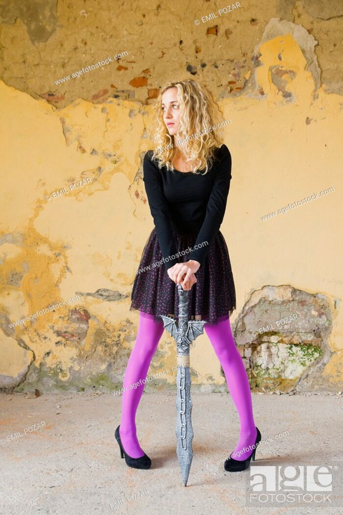 Stock Photo: Standing with a fantasy sword between legs young woman.