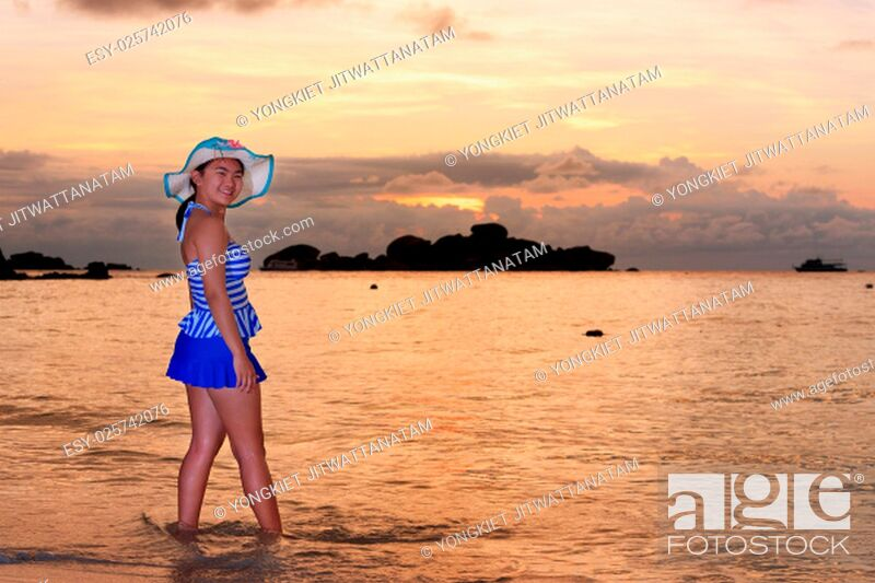 Imagen: Visitors woman in a blue swimwear and hat standing looking the beautiful landscape of sky over the sea happily on the beach during sunrise at Koh Miang Islands.