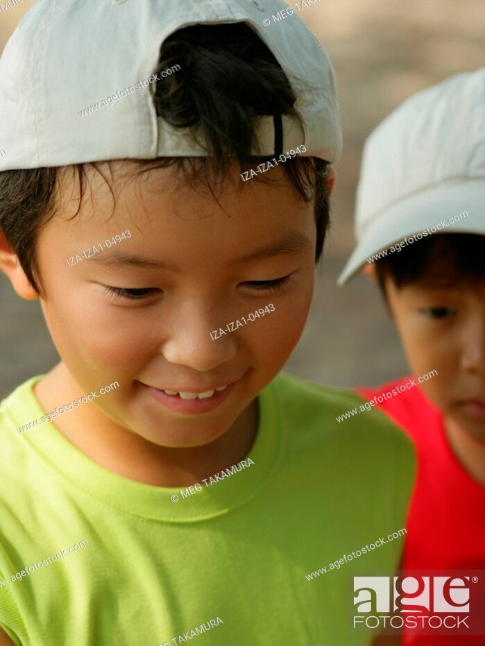 Stock Photo: Close-up of a boy looking down with a boy in the background.