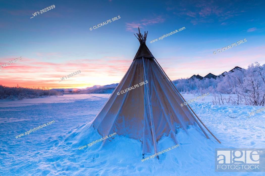 Stock Photo: Pink sky at sunrise on isolated Sami tent in the snow, Abisko, Kiruna Municipality, Norrbotten County, Lapland, Sweden.