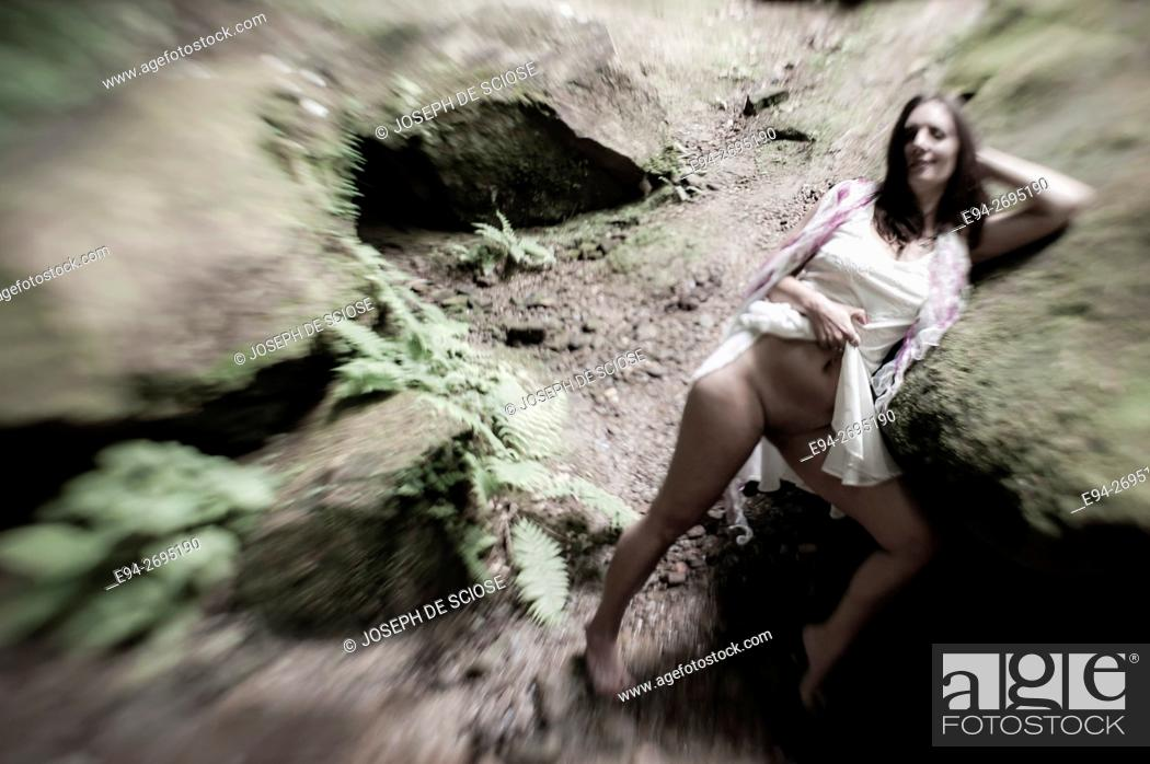 Stock Photo: A partially nude 42 year old brunette woman wearing a white dress and leaning next to a rock in a forest, black and white.