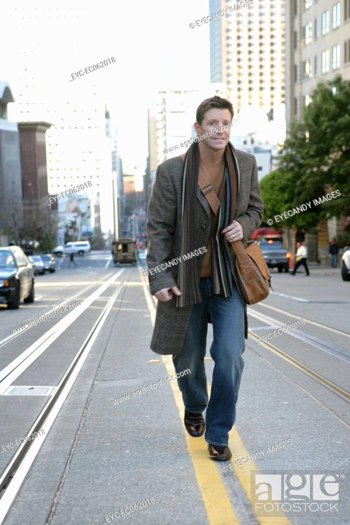 Stock Photo: Mature man walking down the street.