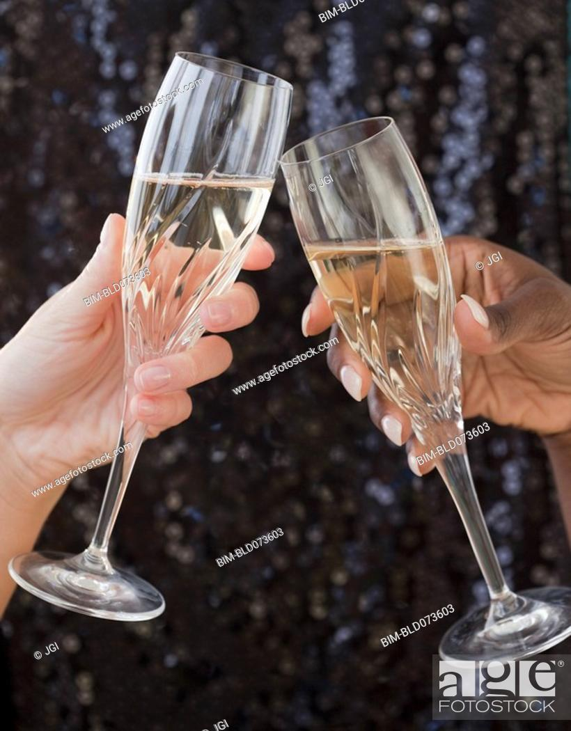 Stock Photo: African and Caucasian woman toasting with champagne.