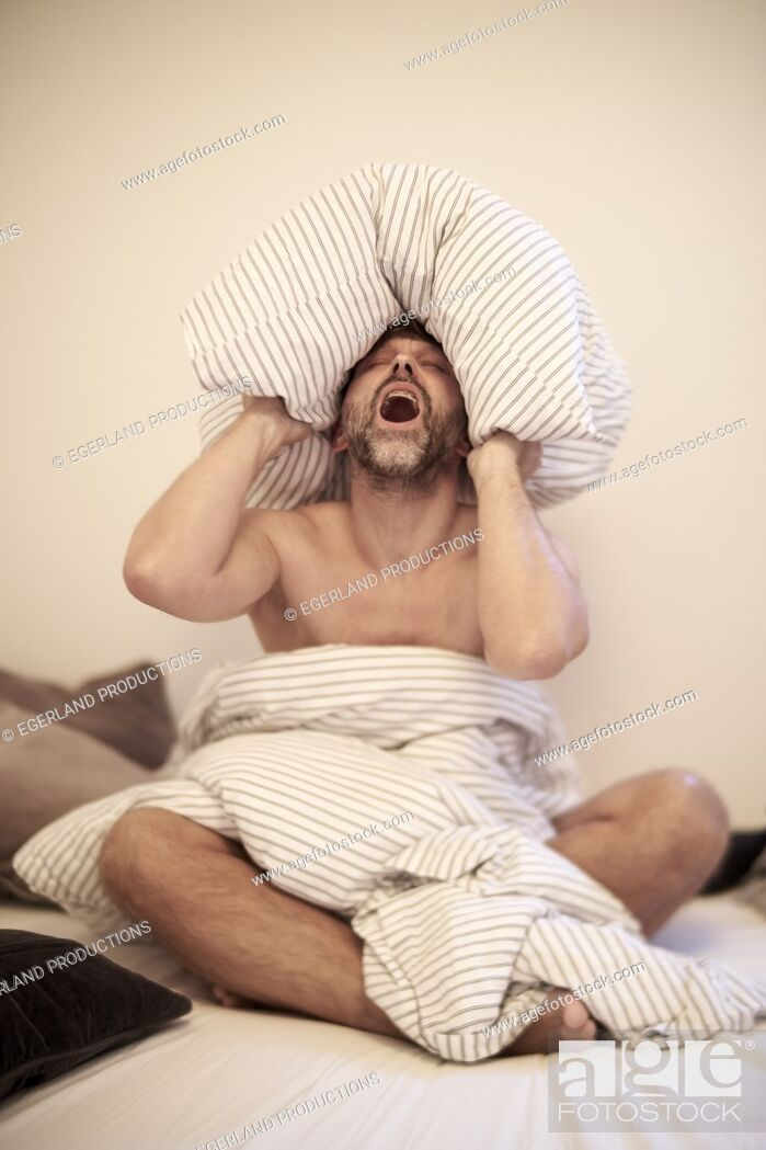 Stock Photo: Nude man sitting on bead with pillow on his head.