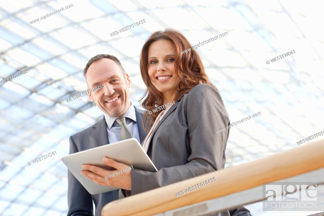 Stock Photo: Germany, Leipzig, Business people using digital tablet, smiling, portrait.