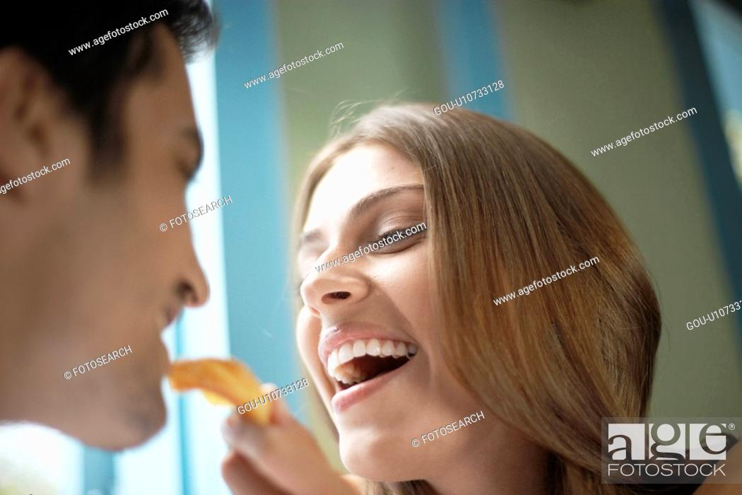 Stock Photo: Woman feeding man with cookie.