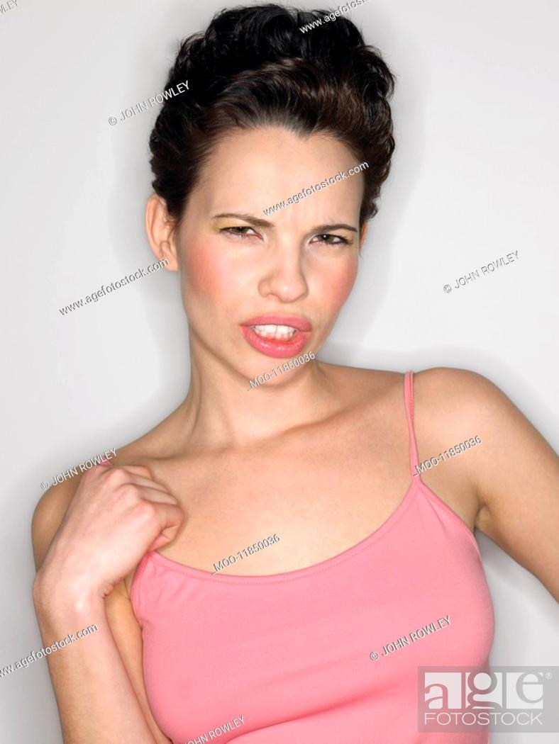 Stock Photo: Woman gritting teeth in studio half-length.