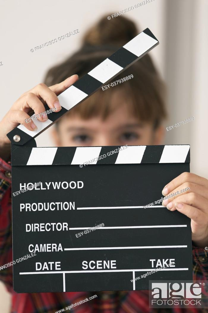 Photo de stock: 10-year-old girl with a clapboard of a hundred in her hands. Vertical shot.