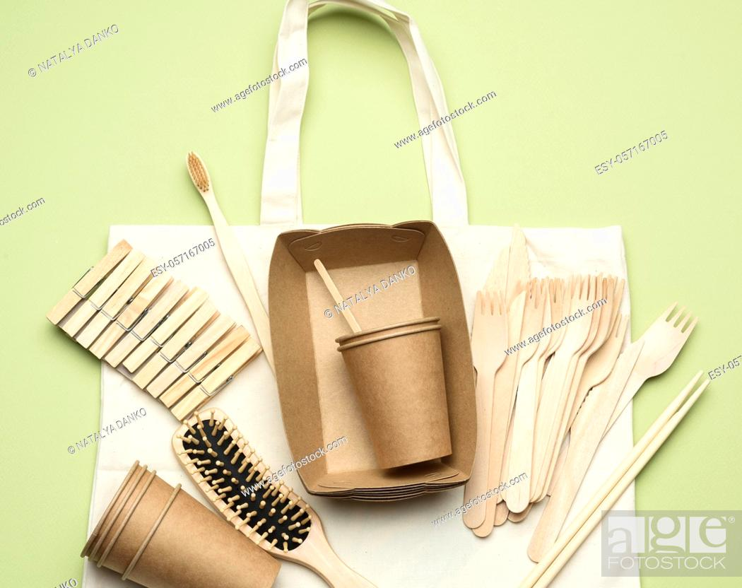 Stock Photo: white textile bag and disposable tableware from brown craft paper on a green background. View from above, plastic rejection concept, zero waste.