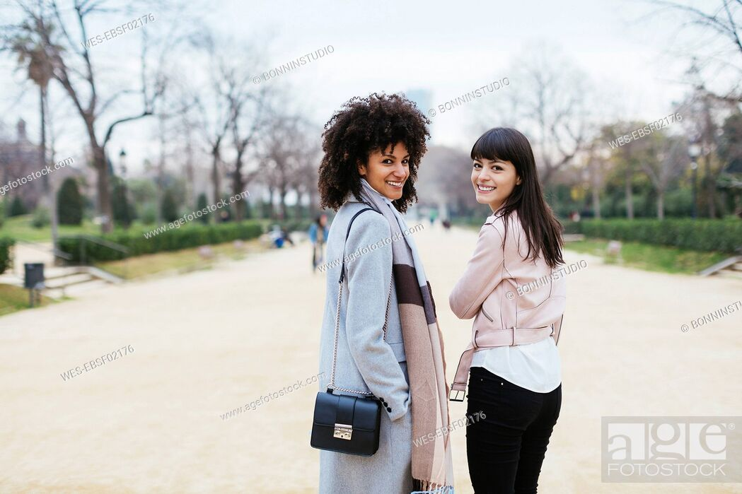 Stock Photo: Spain, Barcelona, portrait of two smiling women in city park turning round.