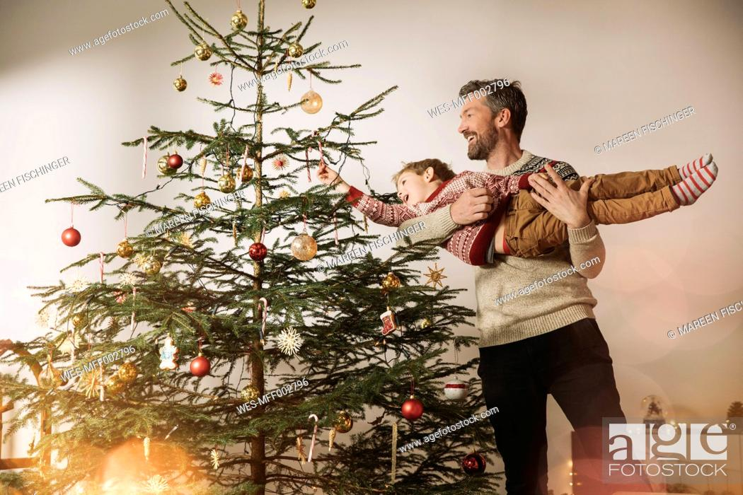 Photo de stock: Father and son decorating Christmas tree.