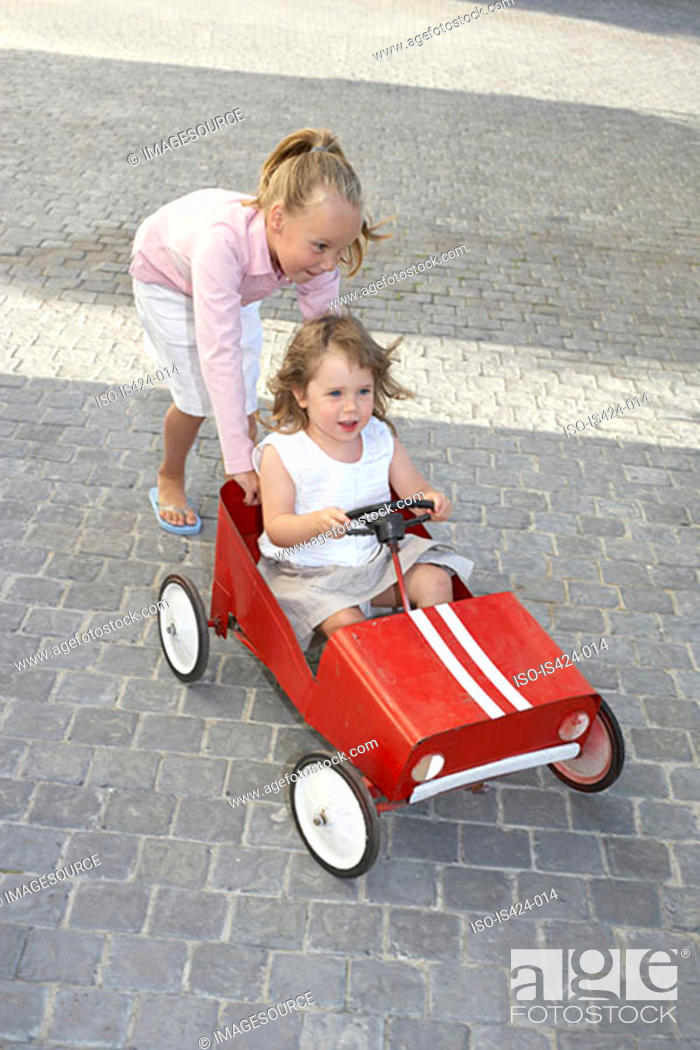 Stock Photo: Sister pushing her younger sister in a toy car.
