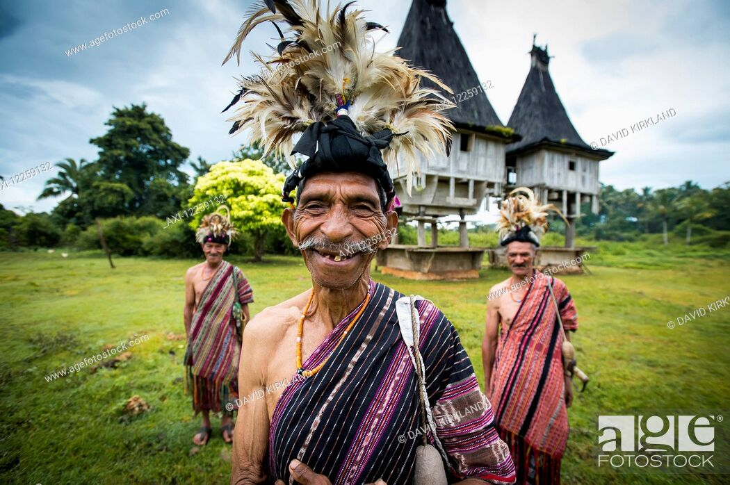 Imagen: Group of men in traditional attire with sacred houses in the background; Lospalmos district, Timor-Leste.