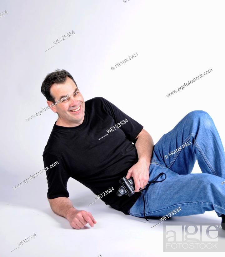 Stock Photo: Man on the floor of studio with a big smile and looking towards the camera.White background.