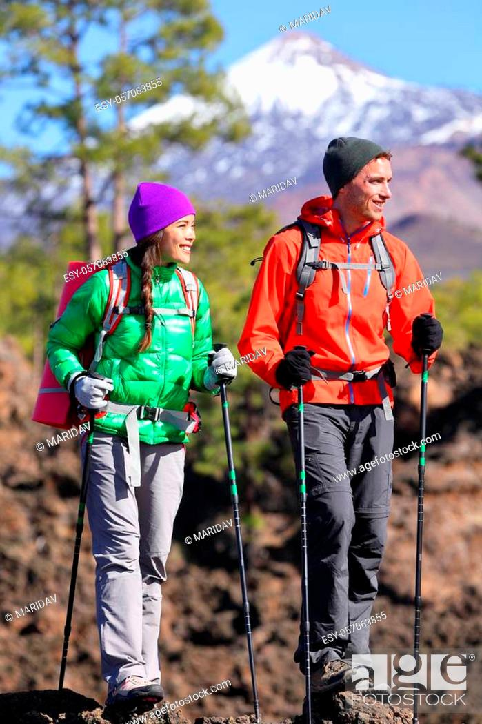 Stock Photo: Hikers people hiking - healthy active lifestyle. Hiker couple hiking in beautiful mountain nature landscape. Woman and man hikers walking during hike on volcano.