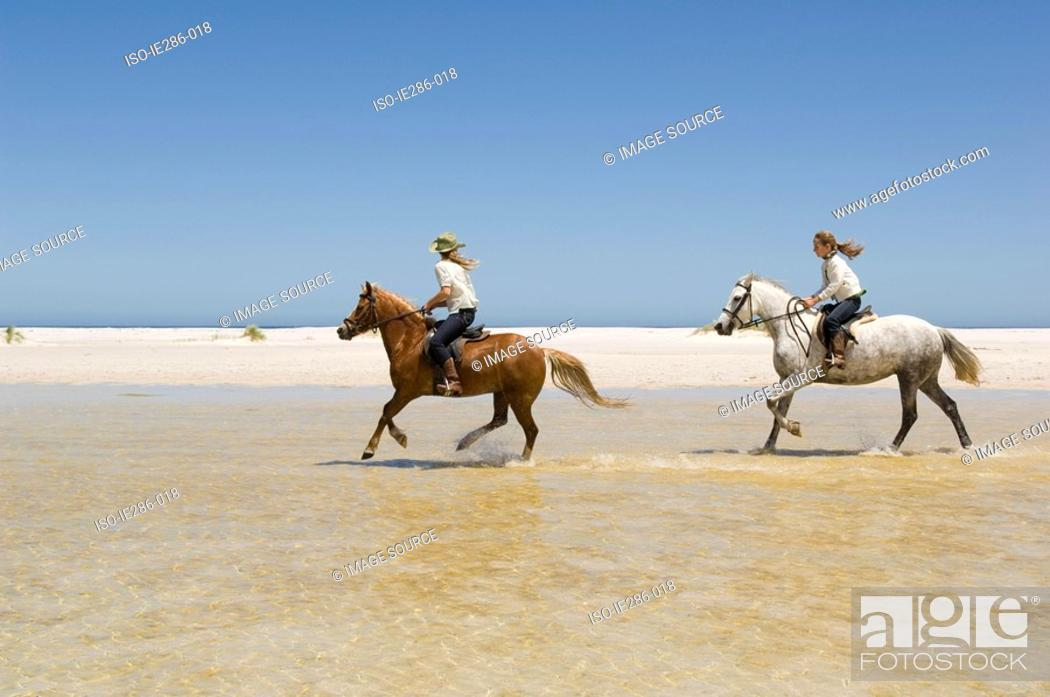 Stock Photo: Two girls riding horses.