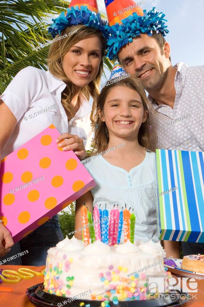 Stock Photo: Portrait of a girl smiling with her parents holding birthday presents.