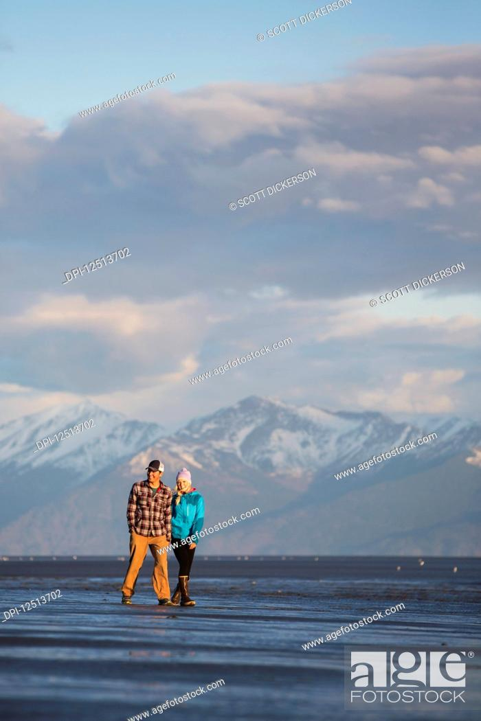 Stock Photo: A young couple walking on a beach and holding hands with a mountain range in the distance; Anchorage, Alaska, United States of America.