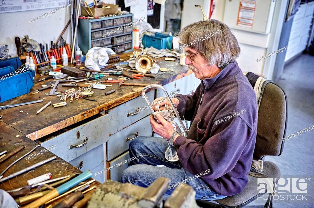 Imagen: Instrument maker repairing trumpet in workshop.