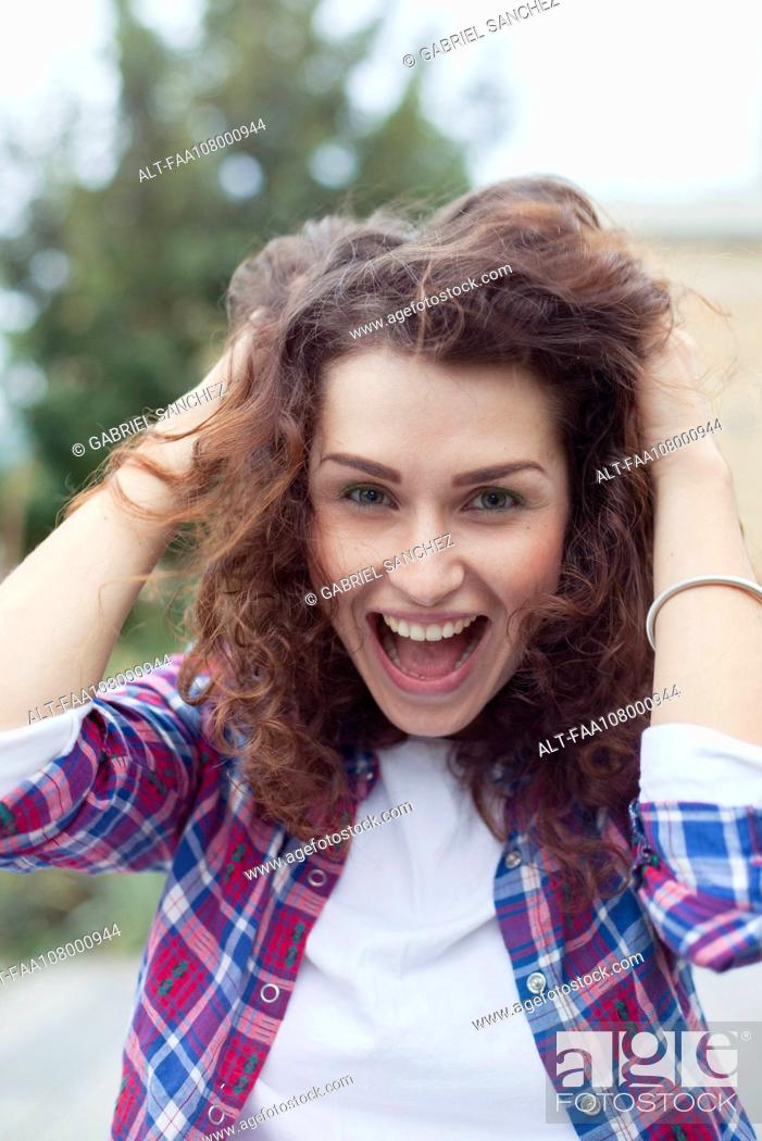 Stock Photo: Carefree young woman laughing outdoors, portrait.