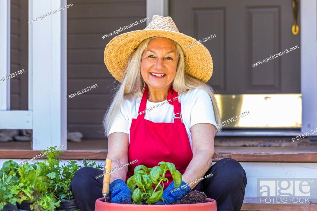 Stock Photo: Caucasian woman planting seedling on front stoop.