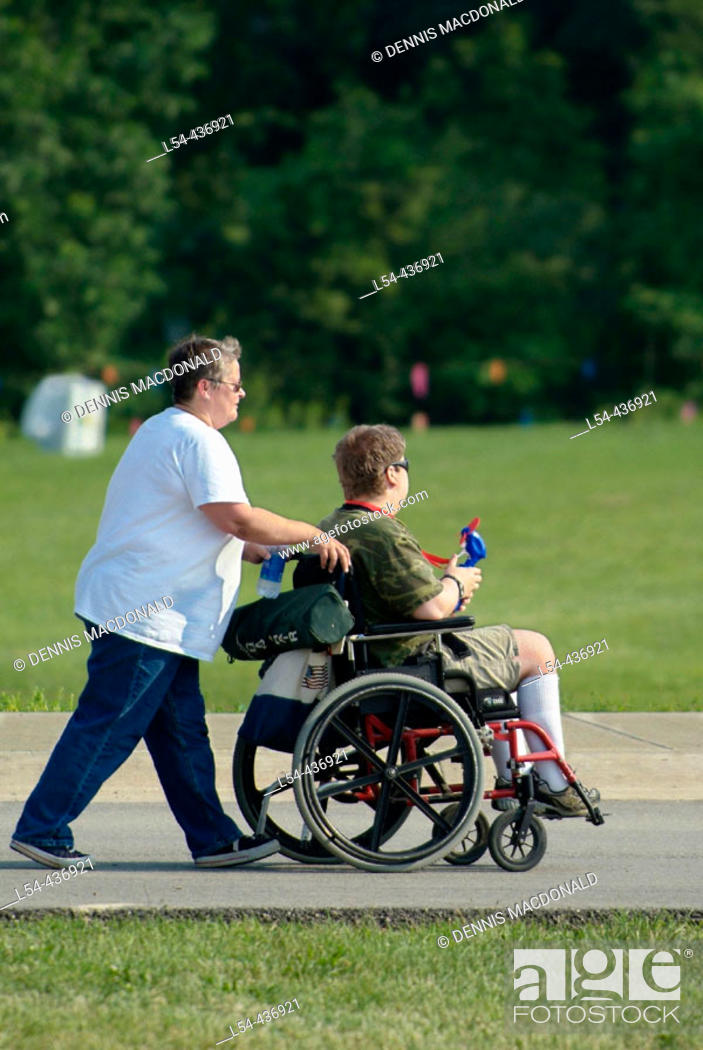 Stock Photo: Handicapped adults ride in a battery powered wheelchair while attending a festival.