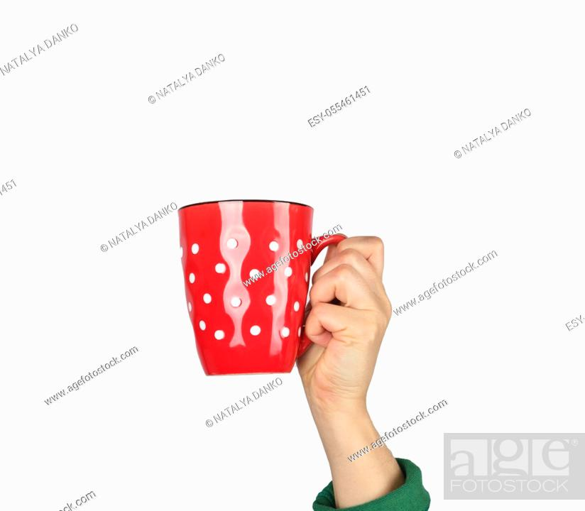 Stock Photo: red ceramic cup in a female hand on a white background, hand is raised up.
