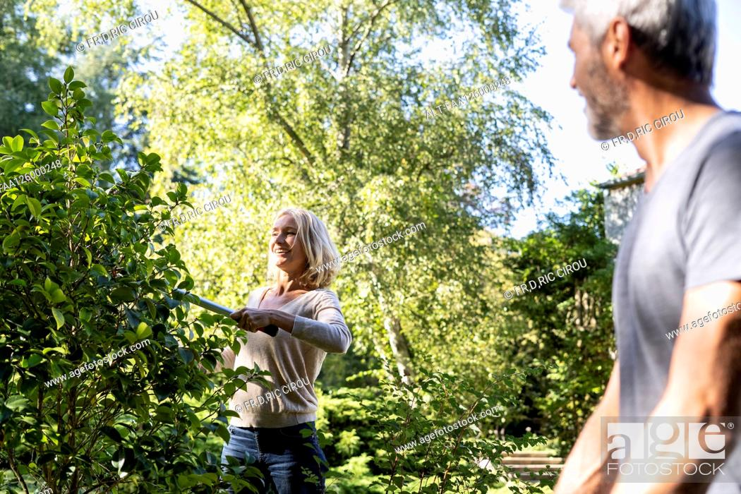 Photo de stock: Smiling mature man looking at his wife pruning plant in backyard.