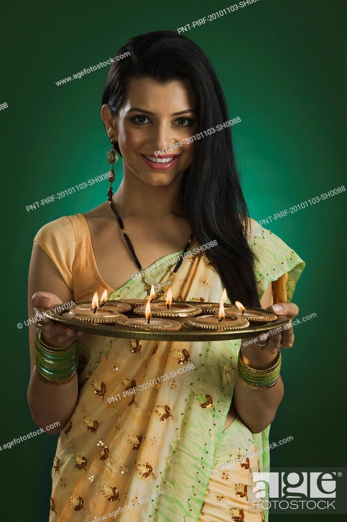 Stock Photo: Woman holding a traditional Diwali thali and smiling.
