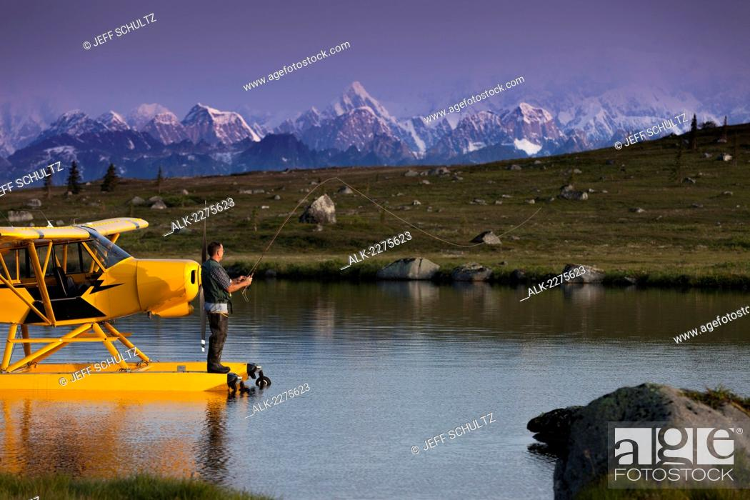 Photo de stock: A pilot fly fishes from his Super Cub floatplane on an unnamed lake in SouthCentral, Alaska with Alaska Range in the background, Summer.