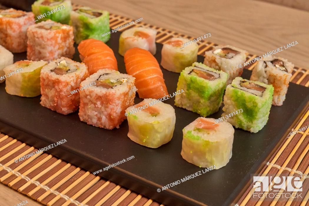 Stock Photo: The range of different types of sushi, rolls, sashimi and Maki with sauces. On black rustic background over wood and mat.